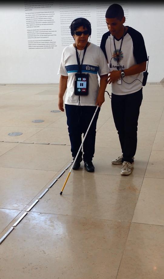pessoa com deficiência visual utilizando audioguia do Museu do Amanhã