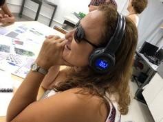 Cida experimentando o equipamento de som colocado sobre os seus ouvidos