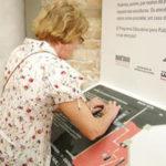 Pessoa com deficiência visual lendo o mapa tátil da Galeria Tátil da Pinacoteca de São Paulo